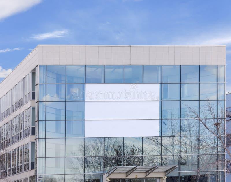 Panneau d'affichage vide sur le nouveau bâtiment en verre moderne pour le loyer et pour des affaires photo libre de droits