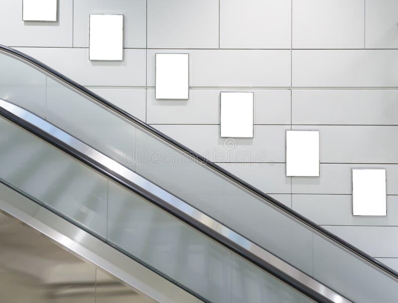 Panneau d'affichage vide vertical avec le fond d'escalator images stock