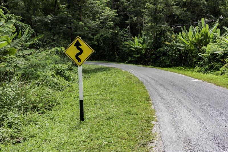 Panneau d'avertissement de courbe le long de petite route photographie stock