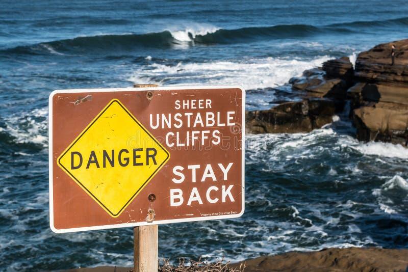 Panneau d'avertissement des falaises instables aux falaises de coucher du soleil images stock