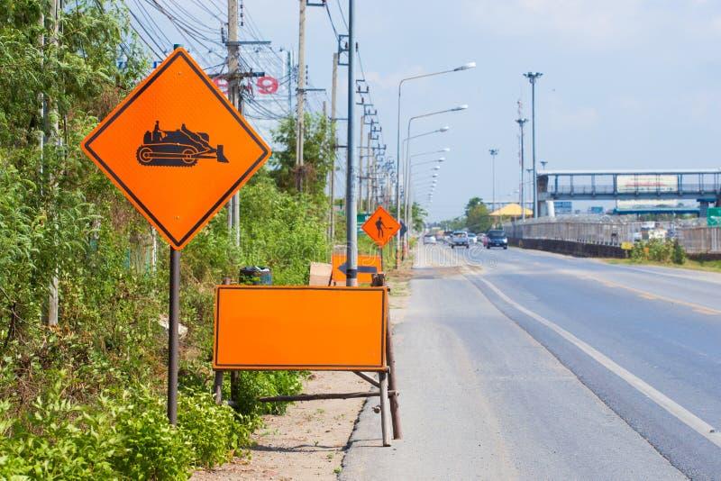 Panneau d'avertissement des véhicules de construction sur la route photos stock