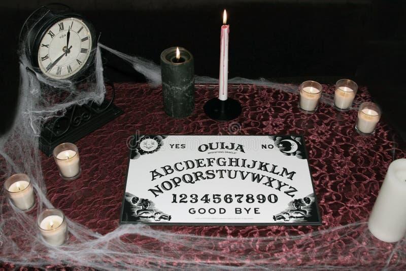 Panneau d'Ouija avec des bougies images stock