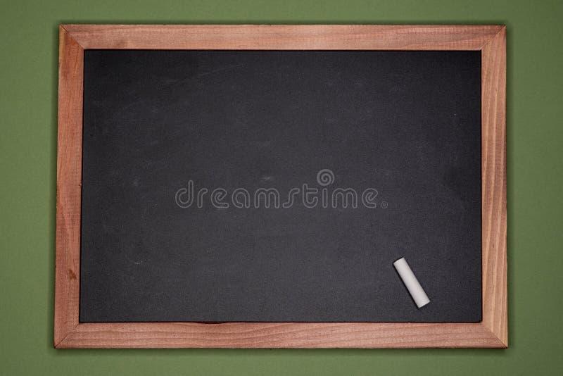 Panneau de craie vide avec le cadre en bois sur le fond vert, l'espace vide de copie photos stock