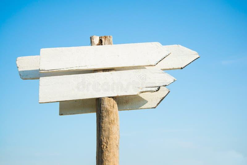 Panneau en bois blanc vide de signe contre le ciel bleu image stock