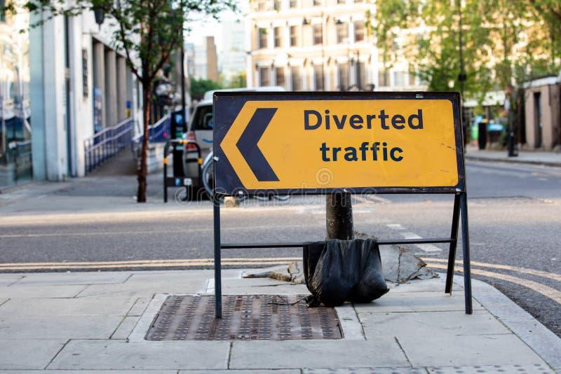 Panneau routier détourné jaune du trafic dans une rue BRITANNIQUE de ville photo stock
