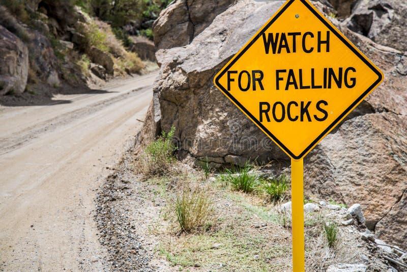 Panneau routier d'avertissement en baisse de danger de roches image libre de droits