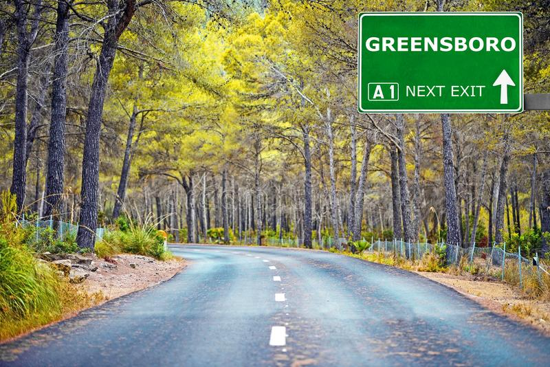 Panneau routier de GREENSBORO contre le ciel bleu clair photographie stock
