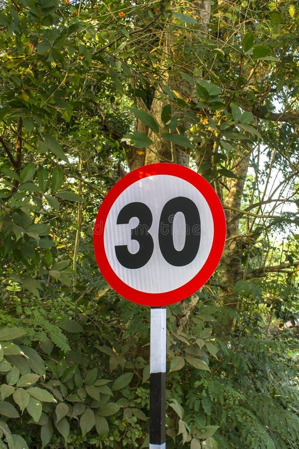 Panneau routier de limitation de vitesse à 30 dans la perspective des arbres et des arbustes verts images stock