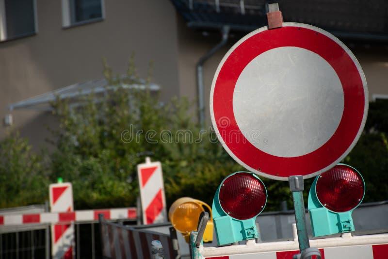 Panneau routier rond rouge avec des lumières de réflecteur avec des barricades bloquant la rue dans le becaue de salon des travau photos stock