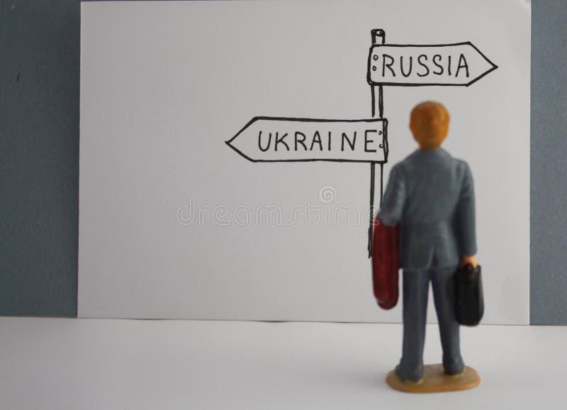 Panneau routier tiré par la main Russie ou direction de l'Ukraine L'homme miniature prenant la décision, choisit entre la Russie  image libre de droits