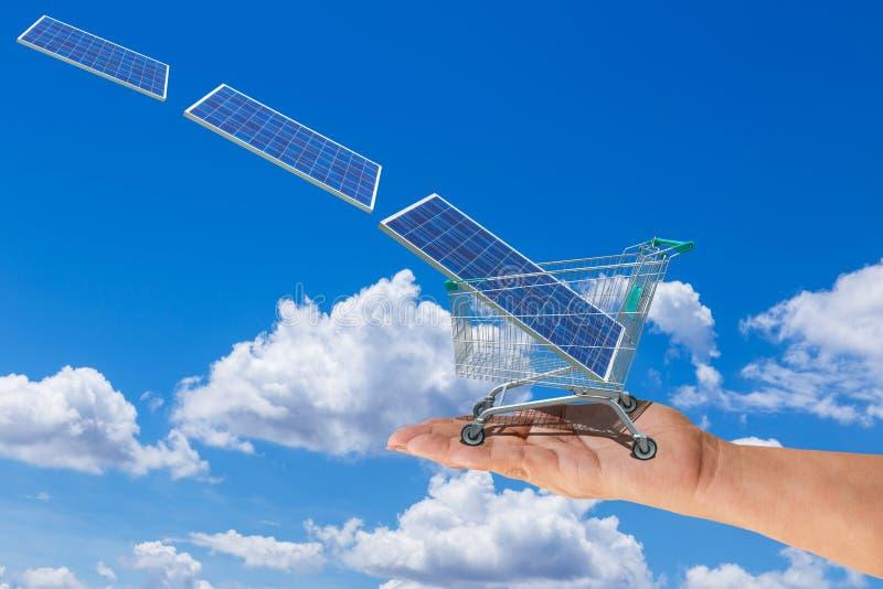 Panneau solaire dans le chariot de chariot à achats sur la main de femmes avec le photovoltaics tombant du ciel photographie stock