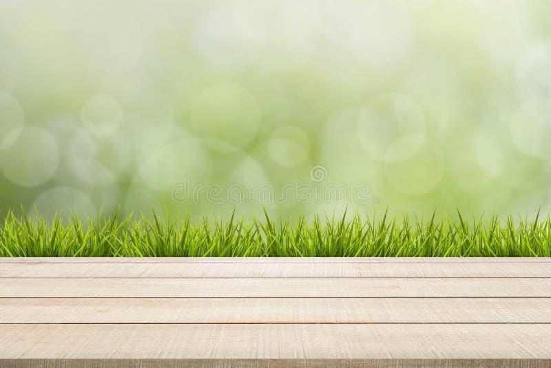 Panneau supérieur et herbe en bois de table sur le fond vert image stock
