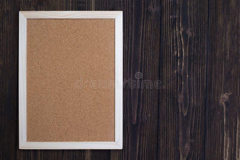 Panneau vide de liège avec le cadre en bois sur le bureau en bois, vue supérieure avec photos stock