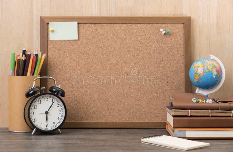 Panneau vide de liège avec le réveil, livre sur le bureau en bois photos libres de droits