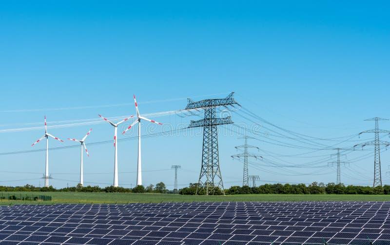 Panneaux à énergie solaire, énergie éolienne et pylônes de l'électricité images libres de droits