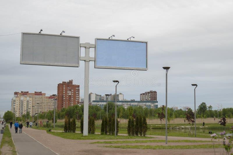 Panneaux d'affichage de grande ville sur le fond de la ville et du ciel du nord nuageux et sombre photos stock