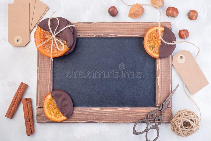 Panneaux de calfeutrage vides avec oranges tranchées confites, noix, corde, ciseaux et étiquette vide, cadeaux sucrés, horizontal images stock