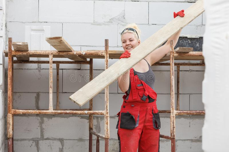 Panneaux de transport de planche de femme sur le chantier de construction photo stock