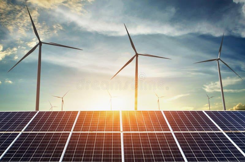panneaux solaires avec des turbines et le coucher du soleil de vent énergie propre de concept image stock