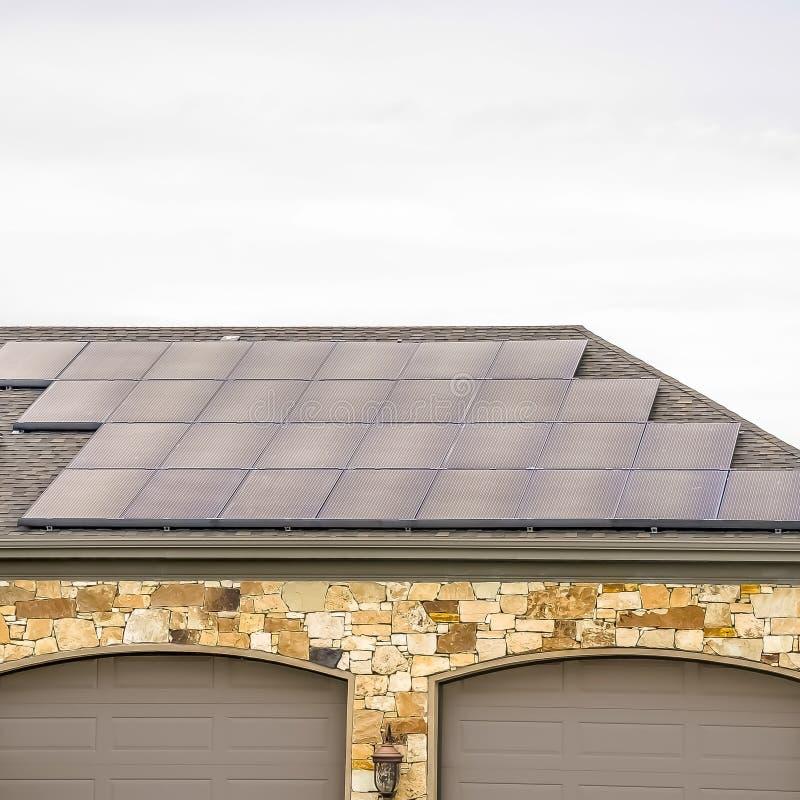 Panneaux solaires de place installés sur le toit de garage d'une maison avec le fond de ciel nuageux photographie stock
