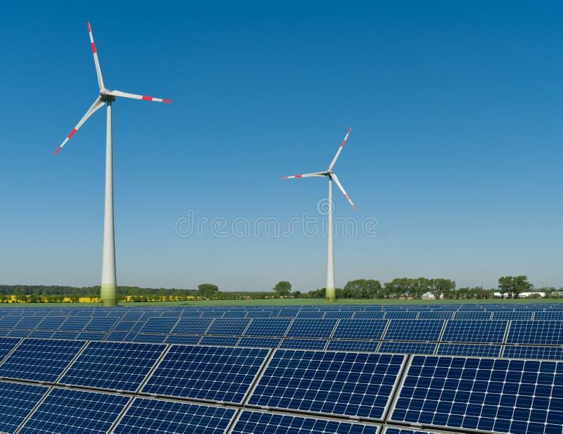 Panneaux solaires et turbines de vent contre une graine de colza photo libre de droits