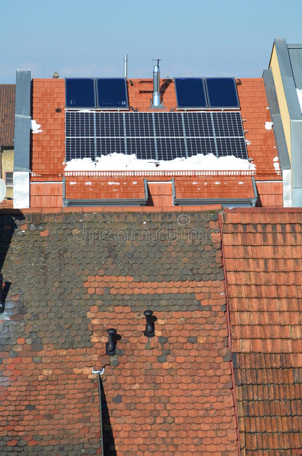 Panneaux solaires sur un dessus de toit en hiver images libres de droits