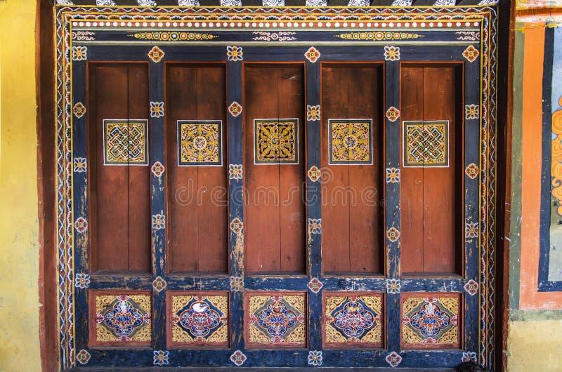 Panneaux traditionnels et fenêtre colorés de Trongsa Dzong, découpant et peignant, art du Bhutan image stock