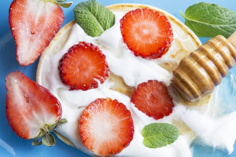 Pannekoek met aardbeien, honing en munt royalty-vrije stock foto