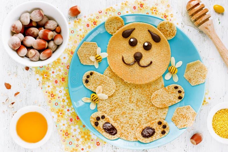 Pannekoeken in de vorm van leuke beer met honing en noten voor jonge geitjes stock afbeelding