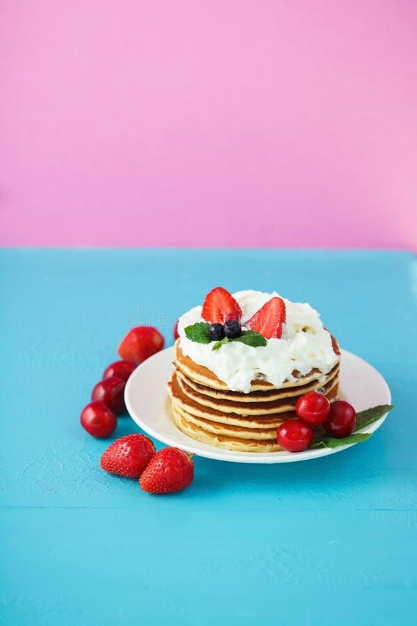 Pannekoeken in een plaat met slagroom, honing, aardbeien, munt en zoete kersen op heldere blauw en roze stock fotografie