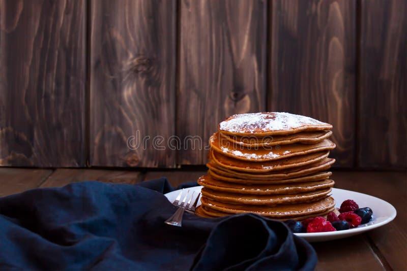 Pannekoeken en bessen met suiker worden bestrooid die stock afbeelding
