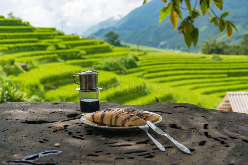 Pannekoeken en koffie met padieveldmening over de achtergrond stock foto
