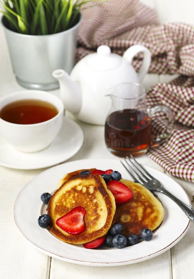 Pannekoeken met aardbeien, bosbessen en ahornstroop stock afbeelding