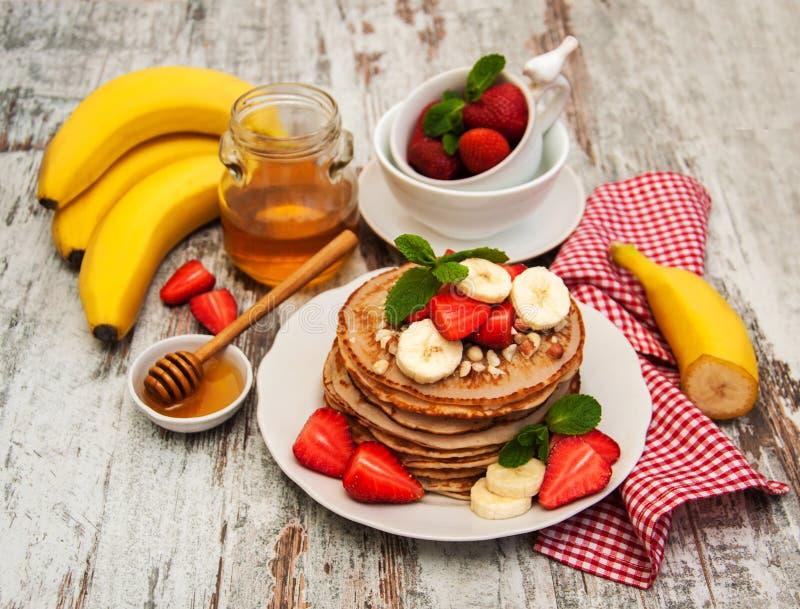 Pannekoeken met aardbeien en bananen stock afbeelding