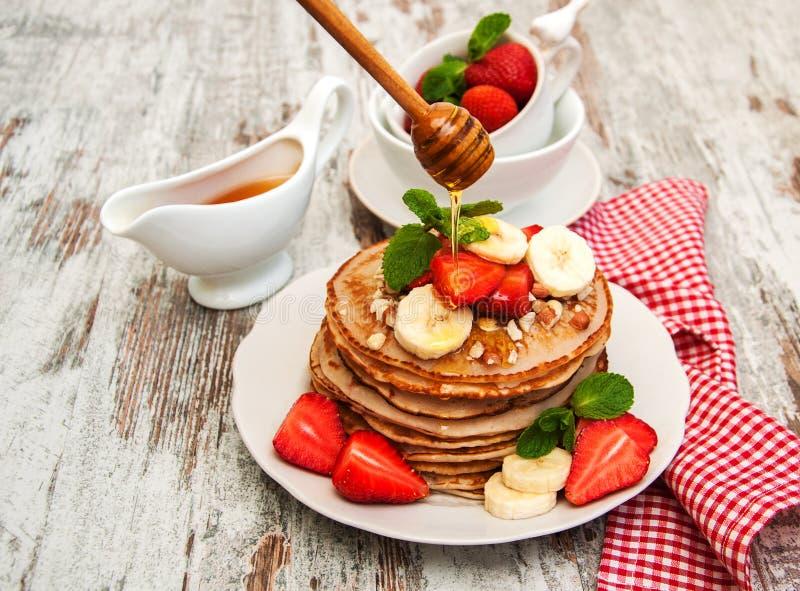Pannekoeken met aardbeien en bananen stock afbeeldingen
