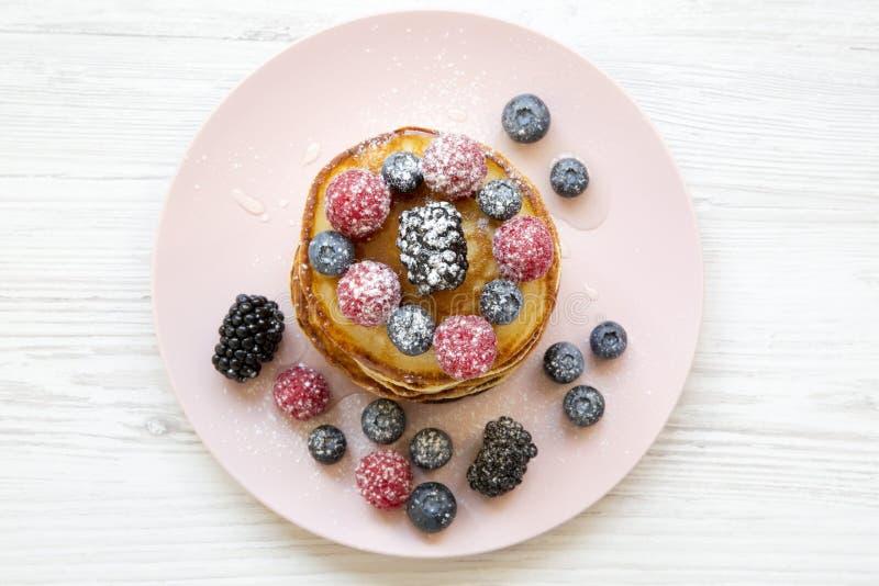 Pannekoeken met bessen, honing en suiker op een roze plaat over witte houten achtergrond, hoogste mening royalty-vrije stock fotografie