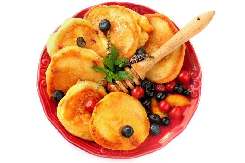 Pannekoeken met bessen, vruchten, honing op een plaat op wit wordt geïsoleerd dat stock afbeelding