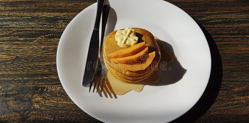 Pannekoeken met boter en mango, met stroop wordt gegoten die royalty-vrije stock afbeeldingen