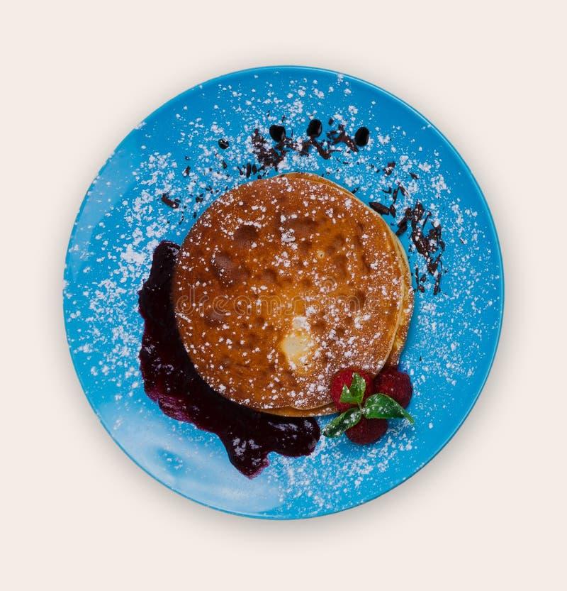 Pannekoeken met frambozensaus op blauwe plaat over witte achtergrond royalty-vrije stock afbeelding