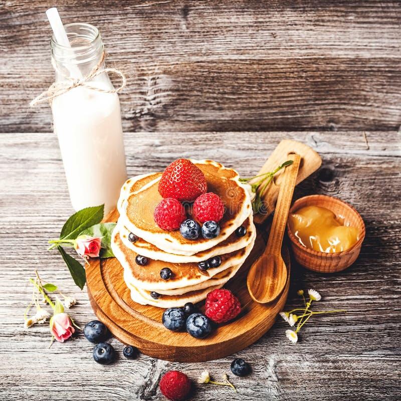 Pannekoeken met verse de zomerbessen en fles melk royalty-vrije stock afbeeldingen