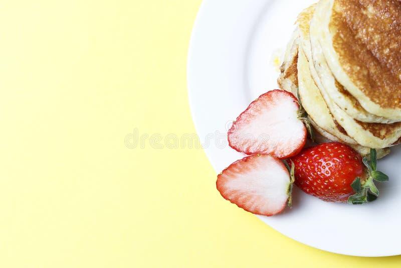 Pannekoeken op een plaat en aardbeien op een gele achtergrond, hoogste mening stock foto's