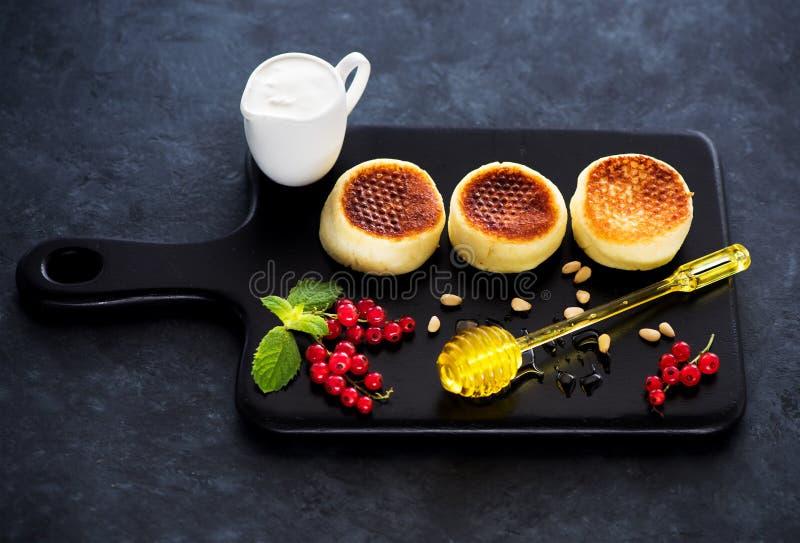 Pannekoeken Syrniki met kwark, bessen, zure room en honing stock fotografie