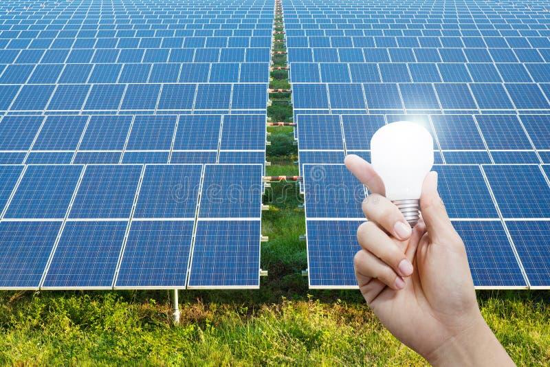 Pannelli a energia solare e lampadina a disposizione, energia fotografia stock libera da diritti