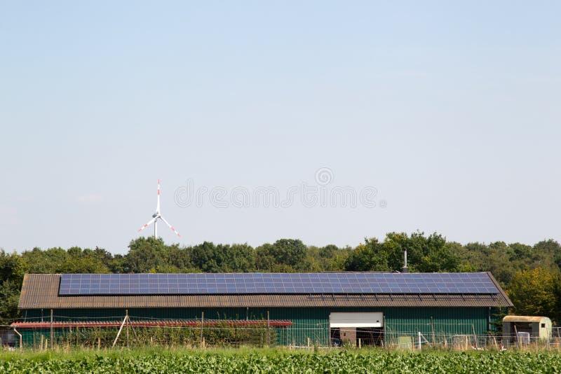 Pannelli solari su fabbricato agricolo con il generatore eolico nel fondo immagine stock libera da diritti