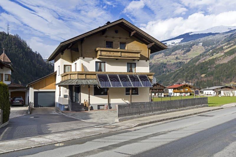 Pannelli solari sulla facciata di un edificio residenziale stile tirolese tradizionale fotografia stock libera da diritti