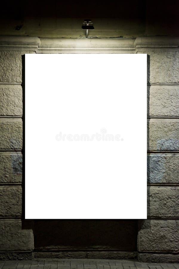 Pannello in bianco di pubblicità su una via Tabellone per le affissioni in bianco illuminato sulla parete Tabellone per le affiss fotografia stock