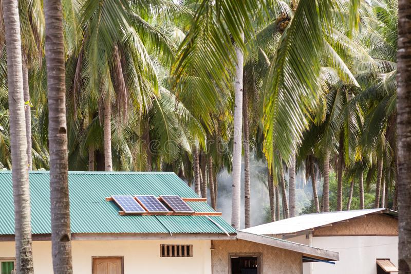 Pannello solare sul tetto della casa con pannelli solari sulla cima Camera nei tropici fra le palme immagini stock libere da diritti