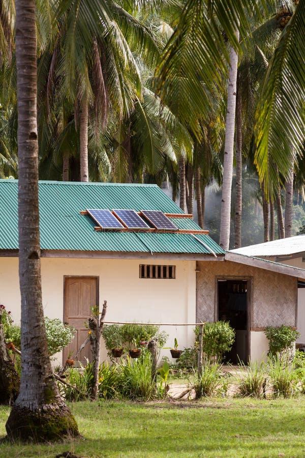 Pannello solare sul tetto della casa con pannelli solari sulla cima Camera nei tropici fra le palme immagine stock