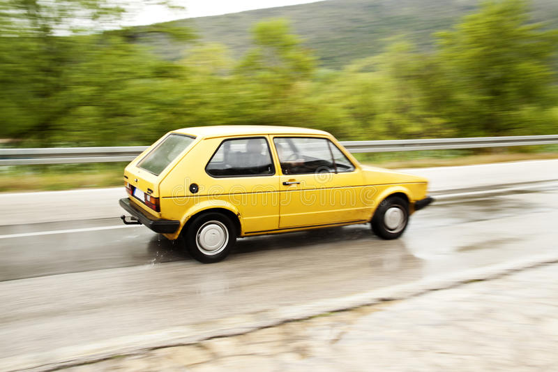 Panning Car. Panning Old Yellow Car on the wet road stock photo