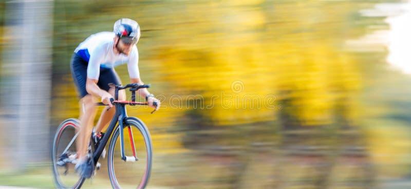 Panning di uno sportivo che va in bici al parco fotografia stock